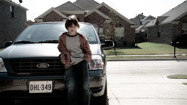 medium shot pre-teen boy leaning on minivan driveway of suburban home - ford motor company stock videos and b-roll footage