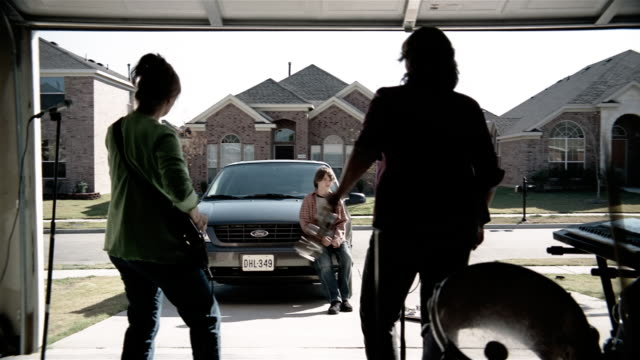 Medium shot pre-teen boy watching rock band of middle age women performing in garage