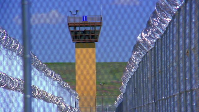 Medium shot prison guard tower / barbed wire and chainlink fence in foreground