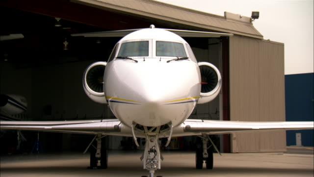 medium shot private jet outside hangar at airport / long beach, california, usa - stationary stock videos & royalty-free footage