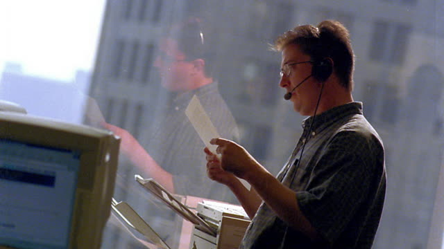 medium shot profile man talking into headset and receiving fax with window in background / boston, massachusetts - 2001 bildbanksvideor och videomaterial från bakom kulisserna