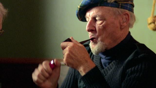 medium shot profile senior man wearing tam lighting pipe, drinking, talking to other man in pub / nova scotia - other stock videos & royalty-free footage