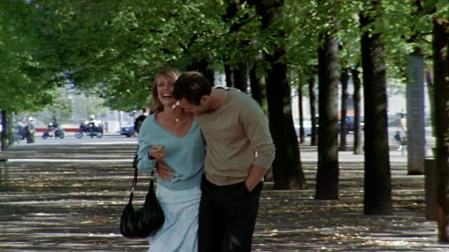 Medium shot rack focus man and woman laughing walking along tree-lined mall