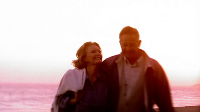 Medium shot rack focus mature couple walking towards camera on beach with sunset and ocean in background / California