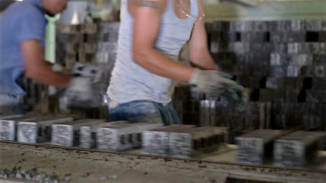 medium shot rack focus pan tilt up men taking bricks off conveyor belt and stacking them in factory - manufacturing occupation video stock e b–roll