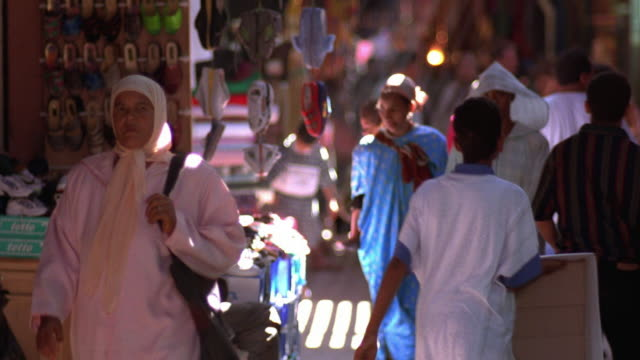 medium shot rack focus people walking past shops in outdoor market / morocco - north africa stock videos & royalty-free footage