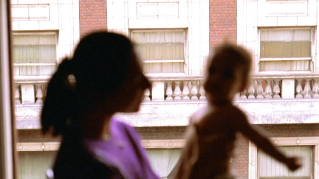 vídeos de stock, filmes e b-roll de medium shot rack focus tilt down tilt up profile woman holding baby in front of window talking and playing with baby / los angeles - foco difuso