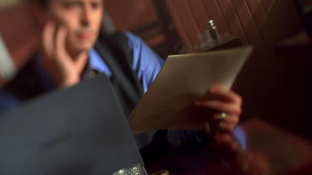 Medium shot rack focus tilt up tilt down frustrated businessman with laptop sitting in empty cafe reading paper / Toronto
