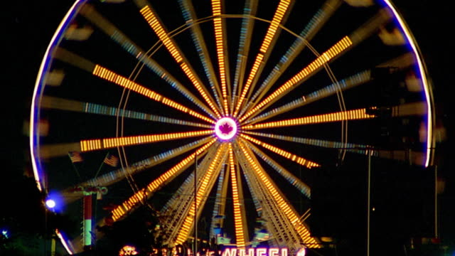 medium shot rack focus time lapse ferris wheel spinning at night / miami, florida - circle stock videos & royalty-free footage