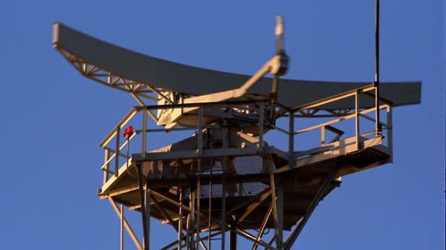 Medium shot radar tower w/spinning transmitter w/blue sky in background