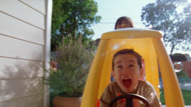 medium shot rear point of view young boy sitting in toy car with girl pushing behind him / california - spingere video stock e b–roll
