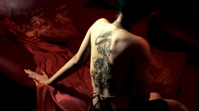 Medium shot rear view Asian woman w/dragon tattoo on back sitting on bed in flickering light