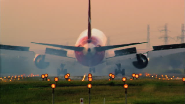 Medium shot rear view commercial jet landing on runway w/lights in foreground