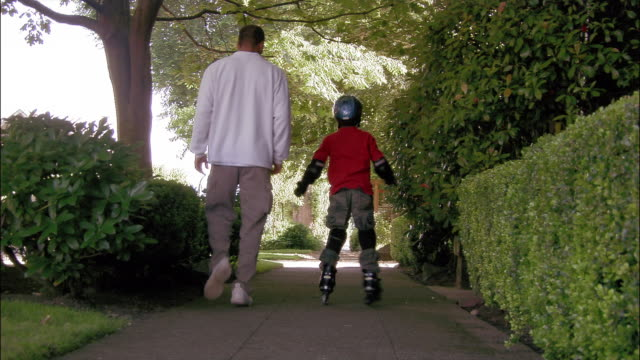 medium shot rear view father running alongside son with roller blades and catching him before he falls - protezione video stock e b–roll