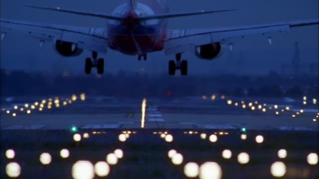 vídeos de stock, filmes e b-roll de medium shot rear view jet landing on runway at night w/lights in foreground - aterrissando