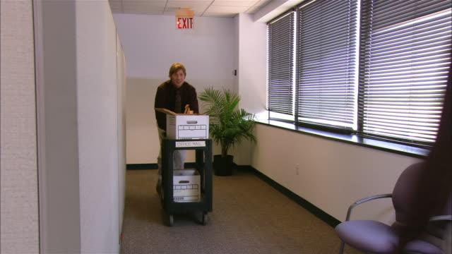 Medium shot rear view man pushing mail cart along corridor / woman passing by and kissing him on cheek