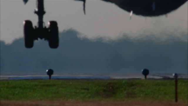 medium shot rear view of airplane touching down on runway - landefahrwerk stock-videos und b-roll-filmmaterial