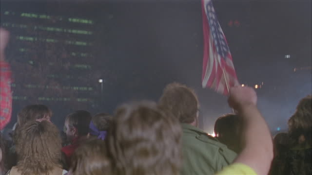 stockvideo's en b-roll-footage met medium shot rear view of anti-vietnam war demonstrators pumping fists and waving upside-down american flag - 1980 1989