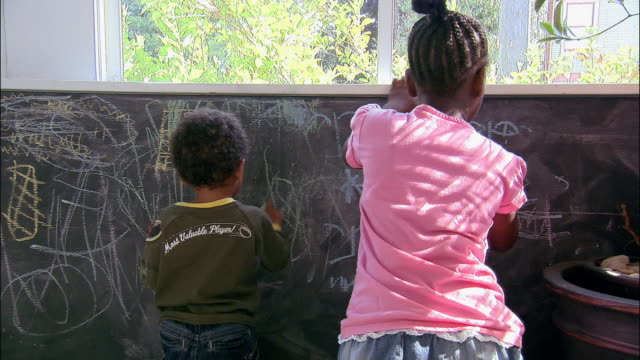 medium shot rear view of boy and girl drawing on chalkboard - scribble stock videos & royalty-free footage