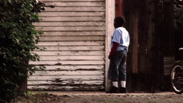 medium shot rear view of boy shooting baskets in driveway - practising stock videos & royalty-free footage
