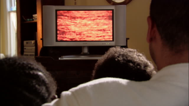 Medium shot rear view of father watching flat screen tv with son and daughter