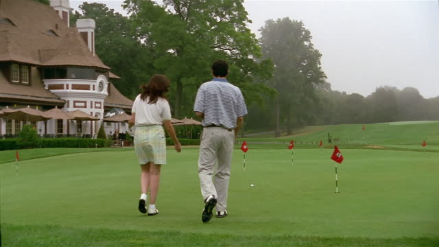 Medium shot rear view of man and woman walking on putting green / woman putting golf + missing