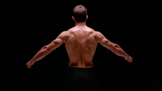 vídeos de stock e filmes b-roll de medium shot rear view of muscular man spreading arms out / lowering arms / london - musculado