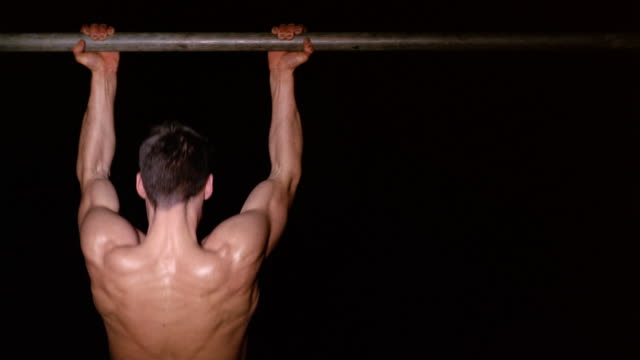 Medium shot rear view of shirtless muscular man doing chin ups on bar