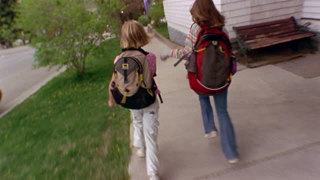 vídeos y material grabado en eventos de stock de medium shot rear view of two girls wearing backpacks running down sidewalk / glenwood springs, colorado - 6 7 años