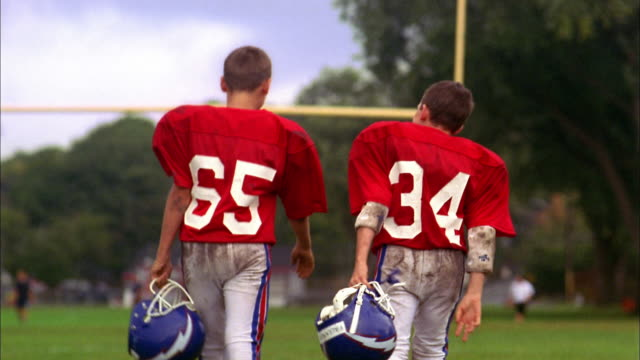 Medium shot rear view of two young boys in football uniforms walking away from CAM