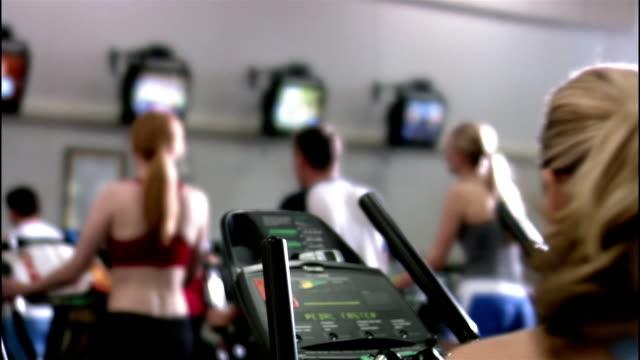 medium shot rear view of woman getting on elliptical trainer at gym - ウィスコンシン州アップルトン点の映像素材/bロール