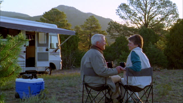 medium shot rear view senior couple sitting and kissing + looking at mountain view w/motor home in background - 50 59 years stock videos & royalty-free footage