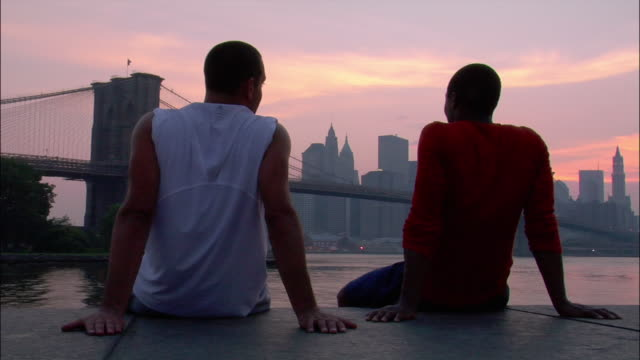Medium shot rear view two men sitting in park watching the sunset over the Brooklyn Bridge / dusk / Dumbo, Brooklyn, New York