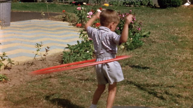 1958 medium shot rear view young boy hula hooping on lawn / turning around toward cam - 1958 stock videos & royalty-free footage