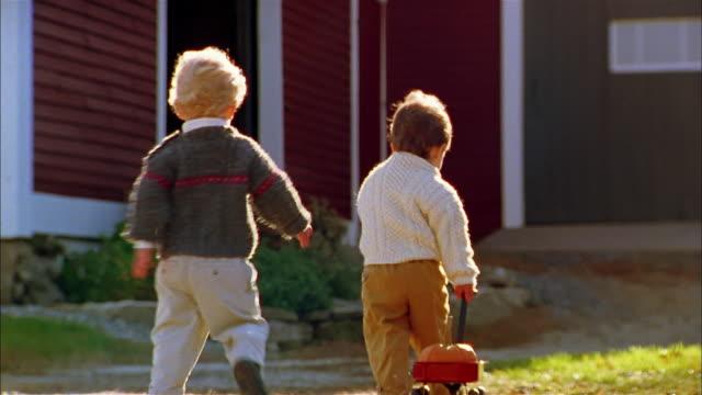 vídeos de stock e filmes b-roll de medium shot rear view young boy pulling red wagon w/pumpkin / other boy running behind him - criança pequena