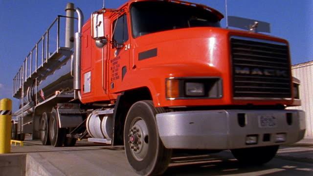 vídeos de stock, filmes e b-roll de medium shot red hazardous materials truck driving past refinery - símbolo de resíduos biológicos