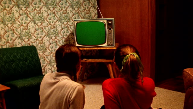 Medium shot REENACTMENT 2 teenage girls sit on floor and watch TV in living room / TV screen is green for use of chroma key