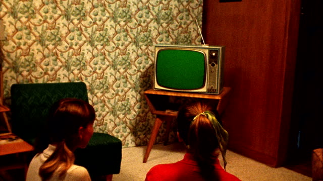 medium shot reenactment 2 teenage girls sit on floor and watch tv in living room / tv screen is green for use with chroma key - television show stock-videos und b-roll-filmmaterial