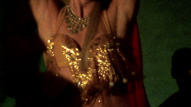 Medium shot REENACTMENT belly dancer performing in red and gold outfit / silhouetted male audience members in foreground
