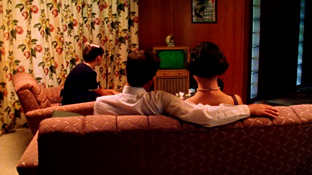 medium shot reenactment family watching tv in living room / tv screen is green for use of chroma key - 1950点の映像素材/bロール