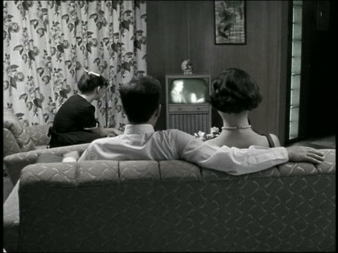 vídeos de stock e filmes b-roll de medium shot reenactment family watching tv in living room with parents on sofa in foreground - 1950