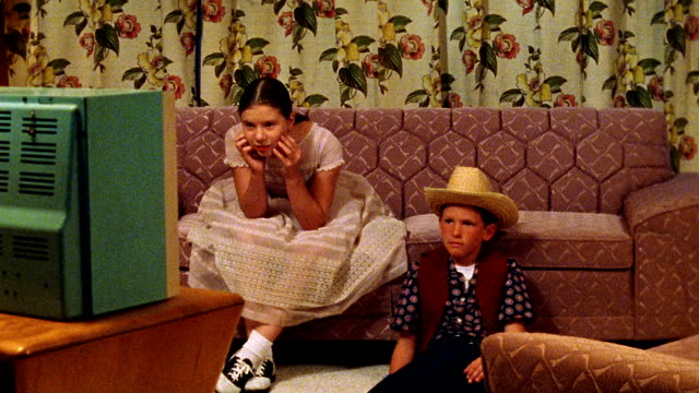 vídeos de stock e filmes b-roll de medium shot reenactment girl and boy laughing + pointing while sitting in front of tv in living room / boy wears cowboy hat - television show