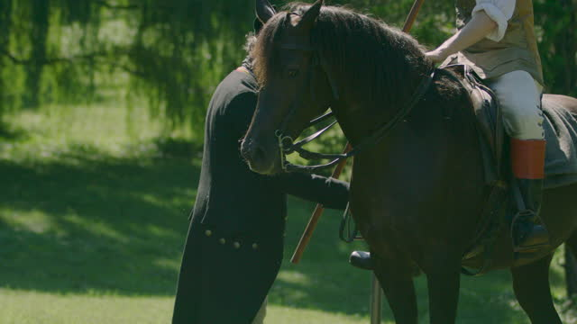 medium shot of a man adjusting the stirrup of a horse rider - bridle stock videos & royalty-free footage