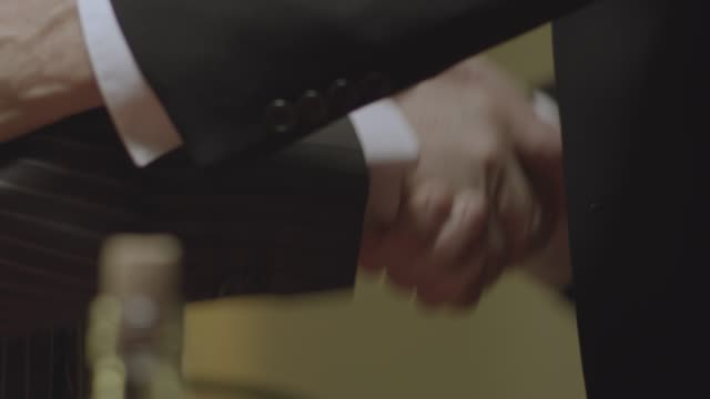 medium shot reenactment of a man in suit shaking hands with a mob boss and toasting with glasses during prohibition - organized crime stock videos & royalty-free footage