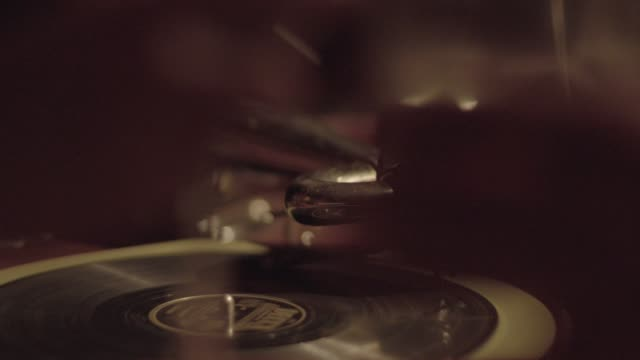 vídeos de stock e filmes b-roll de medium shot of a phonograph playing a record with blurry glasses toasting in the foreground - bar clandestino