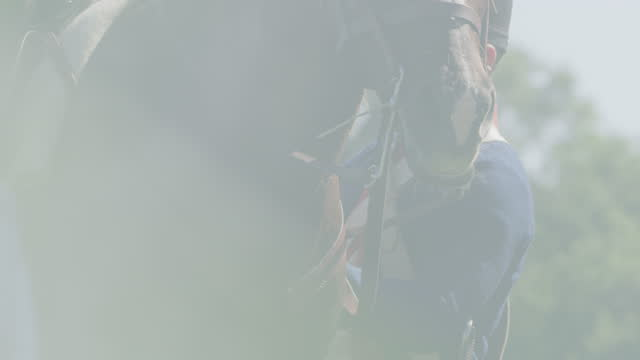 medium shot of a soldier adjusting the stirrup on a horse in the gunpowder smoke - bridle stock videos & royalty-free footage