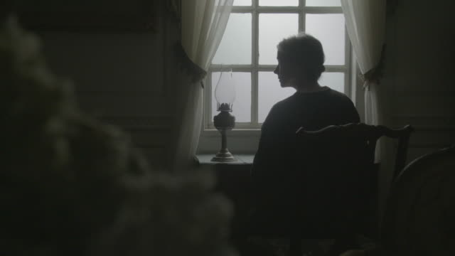 stockvideo's en b-roll-footage met medium shot reenactment of an elderly woman sitting in front of the window and looking up during the civil war era - 18e eeuwse stijl