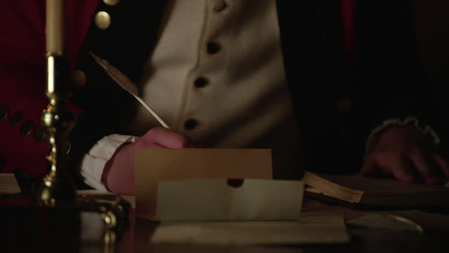 medium shot of the hands of a soldier dipping a quill into ink and starting to write - 金箔点の映像素材/bロール