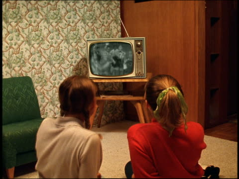 medium shot reenactment two teenage girls sitting on floor and watching dance tv show in living room - television show stock-videos und b-roll-filmmaterial
