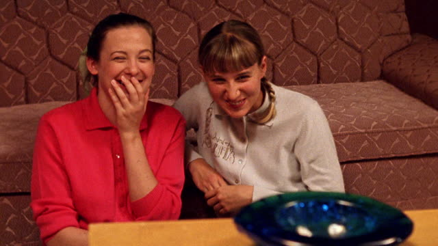 medium shot reenactment two teenage girls sitting on floor, laughing and eating while watching tv in living room - television show stock-videos und b-roll-filmmaterial